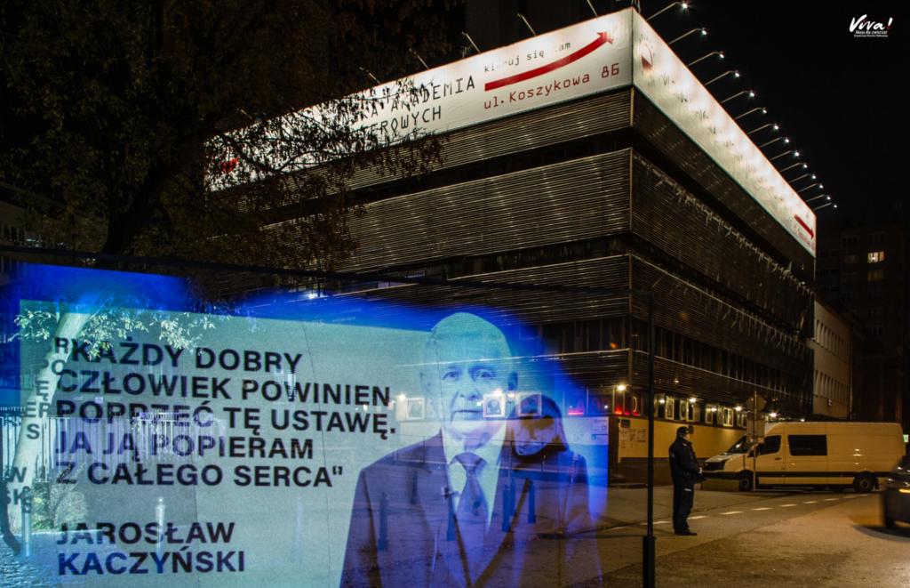 """Hologram pod biurem PiSu, odezwa do Jarosława Kaczyńskiego o szybkie wprowadzenie """"piątki dla zwierząt""""."""